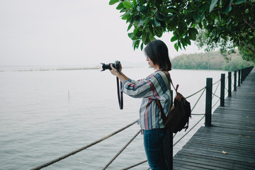 travel background beautiful photographer young women stand alone and hold camera take photo sea view. image for photography, person, portrait, scenery, lifestyle, nature concept