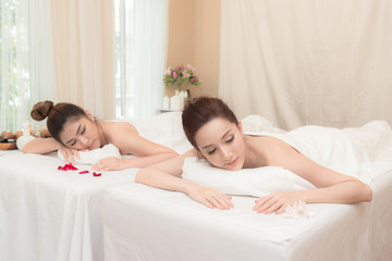 Asian exotic holiday spa concept. Beautiful young chinese woman with her friend enjoy relaxing during massage at spa, taken indoor in real spa location.