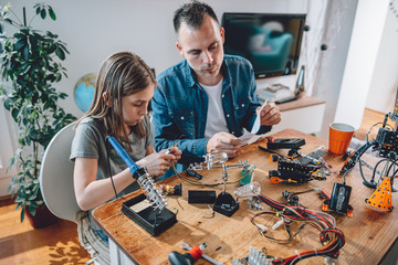 Wall Mural - Father and daughter working on electronics components