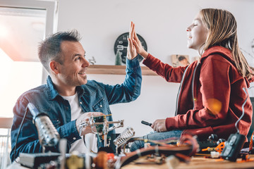 Wall Mural - Father and daughter working on electronics components and cheering