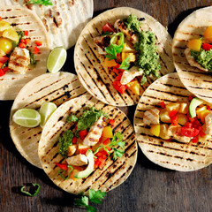 tortilla chicken grilled meat, vegetables avocado sauce on wooden background