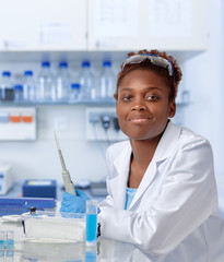 African-american scientist in lab coat and protective gloves
