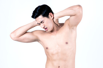 Fitness and health concept. Fit sport man having neck injury, isolated on white background in studio. Half naked Asian chinese lean muscular male wearing a black shorts.