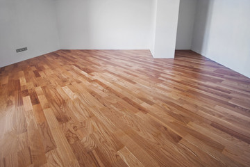 Flooring from a parquet oak board in an interior with bright light from a window.