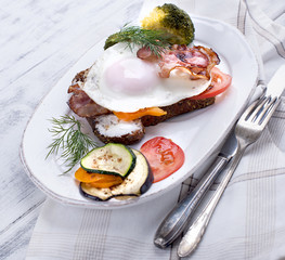 white plate with toast with bacon and vegetables and egg, on a white wooden background