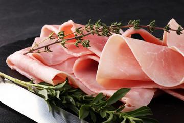Sliced ham on stone background. Fresh prosciutto. Pork ham sliced.