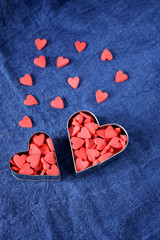 Many little hearts are forming two big ones on a blue background