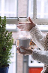 girl in scarf, mug of coffee with steam, near window Christmas tree