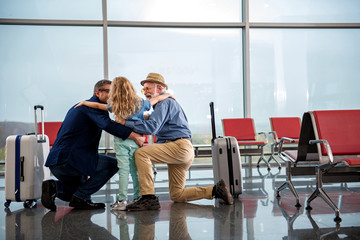 Full length back view of little girl is hugging her adult father and positive grandfather at airport lounge. They are expressing happiness while looking at each other with smile. Copy space