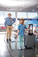 My first travel. Full length portrait of cute little girl is holding suitcase while looking at camera with joy. Her pleasant aged bearded man is resting on walking stick in background. Selective focus