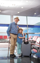 Full length portrait of optimistic gray-haired grandfather and his little granddaughter are standing together at airport lounge. They are looking at camera with smile while girl is holding suitcase