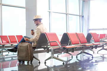 Full length side view profile of cheerful middle-aged tourist in glasses and hat is sitting on red seat of airport and drinking coffee while looking at screen of mobile phone. Copy space in right side