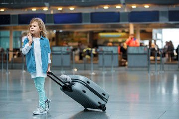 First journey. Full length of stylish cute blond child is standing at airport building and carrying her suitcase with toy bear. She is looking aside pensively while waiting for flight. Copy space