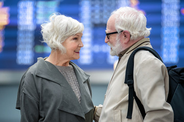 Together abroad. Side view profile of stylish romantic aged couple is standing against electronic board at airport building. They are looking at each other with love while man is holding backpack