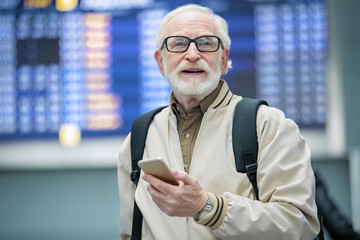 Full of positive emotions. Portrait of cheerful bearded gray-haired man is standing at airport and holding mobile phone while looking aside with smile. Flights departures in background. Copy space