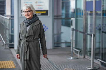 Ready for joyful travel. Portrait of optimistic aged woman is standing near airport building with suitcase while looking at camera with slight smile. Copy space in the right side
