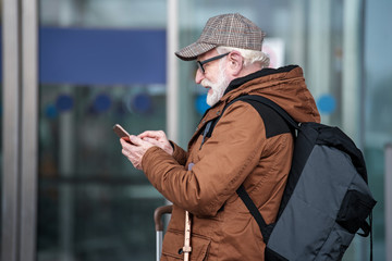 Always connected. Side view profile of pleasant bearded old man in glasses is standing with backpack and using mobile phone while sending message. He is looking at screen with smile