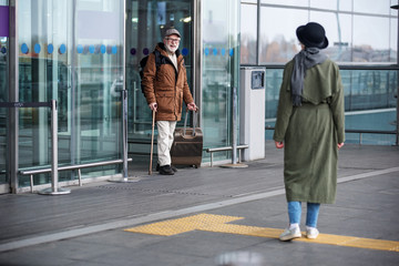 Finally together. Full length of senior man is exiting from airport building while carrying suitcase. He is expressing gladness while seeing stylish woman who is waiting for him. Back view of lady