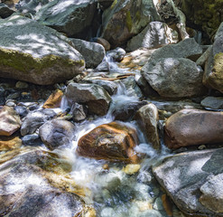 colorful stones in the clear cold water of a creek
