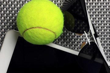 Creative Set Tennis ball, tablet computer and black sunglasses, close-up, on metal background.