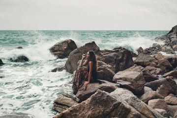 Beautiful young boho styled woman sitting on a stone beach