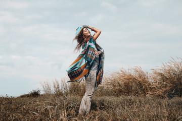cheerful boho woman wearing poncho on field
