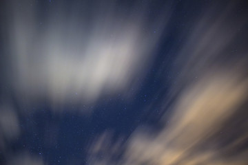 Stars in the night sky background with clouds on a long exposure