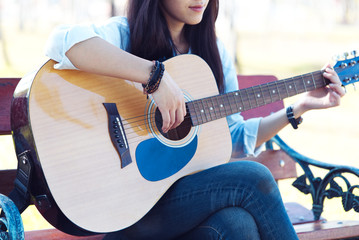 A young girl is playing guitar and sing a song in grass field at relax day with sun light.