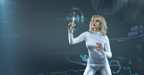 Attractive Blonde model in futuristic environment working with virtual hud interface