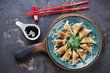 Turquoise plate with pan fried gyoza and seaweed salad on a rustic wooden serving board, brown stone background, top view