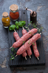 Black wooden chopping board with raw cevapcici or skinless beef sausages on skewers and seasonings, selective focus, vertical shot