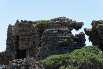 Teilweise bewachsendes Felsgestein am Strand ragt in den blauen Himmel
