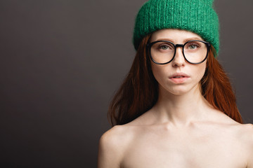 fashion naked redhead Girl in green Knitted Hat and galsses on grey background