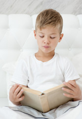 boy is reading a book on the  bed