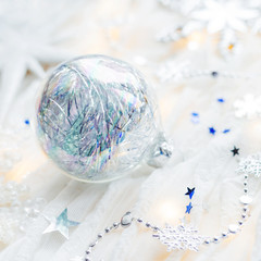 Christmas and New Year holiday background with decorations and light bulbs. Silver and blue shining balls, snowflakes and star confetti.