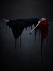 Beautiful red haired woman in black dress and blood lying on the stone.