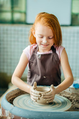 redhead girl sculpts from clay pot. workshop on modeling on potter's wheel.