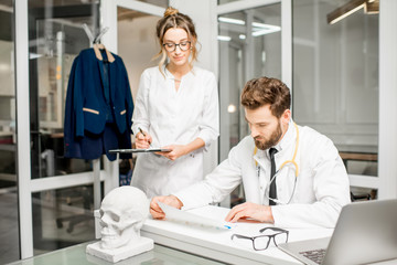 Senior doctor with young female assistant working with medical documents at the white office interior