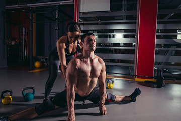 beautiful girl, the coach helps the splits man a naked torso. stretching, cross fit