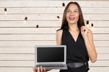 Happy businesswoman standing with laptop