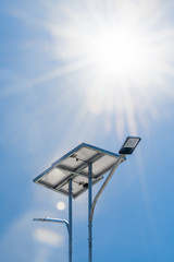 LED street light with solar cell and sun, sun light, lens flare in blue sky background. Green energy concept.