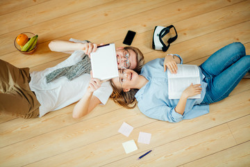 Couple students studying while lying on floor at home