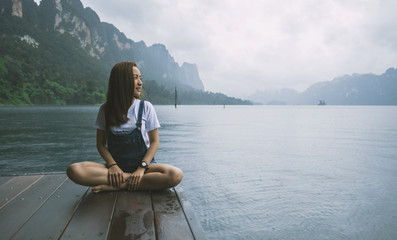 beautiful girl sit alone smile relax on the wood pier in rainy season with vacation time in location lake view