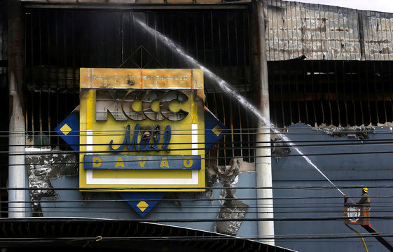A fireman uses a water hose at a shopping mall hit by fire in Davao