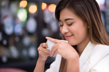 Young businesswoman sitting and drinking coffee happily outside the office at lunch break. Relaxation, Coffee Break, selected focus