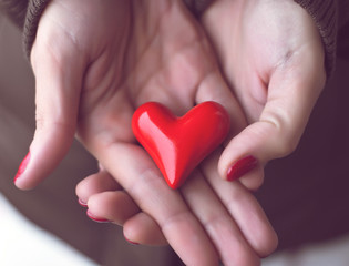 Red heart in woman hands, symbol of love