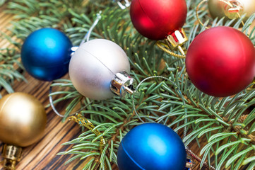 Christmas balls with branch of fir tree on the wooden table. New year background.