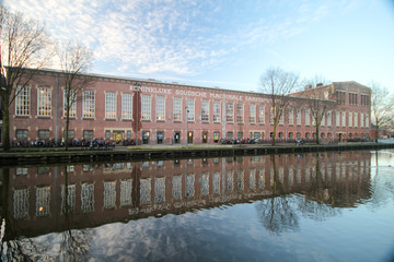Restaurated factory named garenspinnerij mirrors in canal water in Gouda, Netherlands