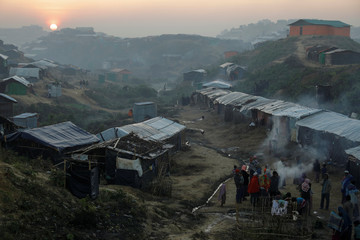 The sun rises as Rohingya refugee gather around a fire at the Palongkhali refugee camp near Cox's Bazar