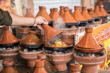 Preparing food in tajin traditional dish in Morocco - meat and vegetable in a ceramic tajine.